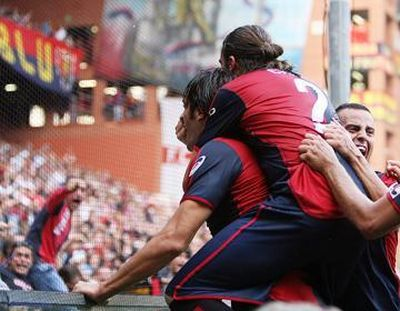 The players of Genoa celebrate the deciding goal of Luca Toni in the 95th minute