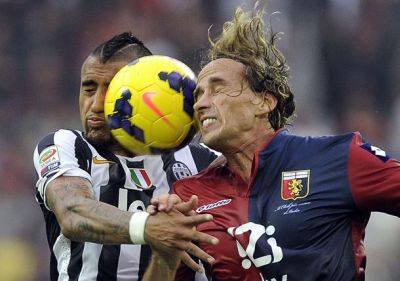 Juventus' Vidal jumps for ball with Genoa's Manfredini during Serie A soccer match in Turin